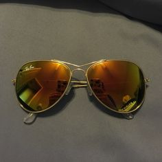 RayBan Aviators Orange-yellow-pinkish mirrored raybans. one small scratch on lens but can hardly tell. also one of the behind the ear pieces is a little rough. Really cute on just have a different pair that I wear more so selling these. Will take any reasonable offer! Ray-Ban Accessories Sunglasses