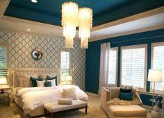 une chambre en blanc et bleu, deco peinture bleu paon, lustres, papier peint a motifs geometriques, moquet beige, lit en beige et blanc