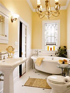 The light and airy feel of this bath springs from the soothing color palette and stained-glass window. The chandelier adds a striking touch.