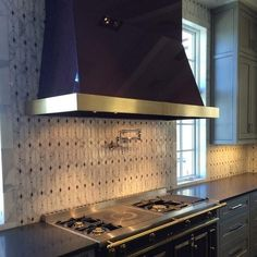 This image from @architecturaltileandstone caught our eye because it tells a unique #design story. Touches of #purple #glass in the #mosaic #backsplash tie into the purple range and hood. The use of this #color is daring yet it's carried out in a classic sophisticated way. Credits: @caesarstoneus perimeter counters @artistic_tile custom Valencia #tile design by @bravointeriordesign / #tiletuesday #kitchen #mosaics #kitchendesign #interior #interiors #interiordesign #interiordesigner…