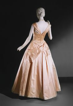 ball gowns were engineered to be sublime sartorial sculptures and were usually fashioned of lustrous heavy silk satin that forgave no mistakes in either pattern or stitching. Nevertheless, the shaping was so calculated that James's garments often integrated features that were extraneous in less analytical clothing. The bow at the back of this gown is not applied; rather, it is cut in one with the skirt front and thus becomes integral with it.1948  Medium: Pink silk satin