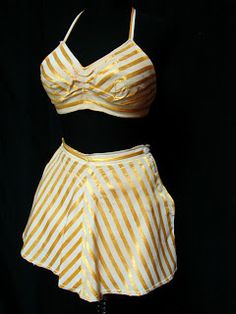 ~A drop dead 1940's vintage pinup swimsuit with a yellow/gold satin stripe. The skirt has inserted jersey cotton panties and the halter top is lined in the same fabric. The skirt has side button closures~