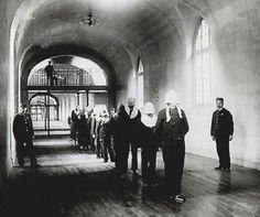 Détenus portant le capuchon belge, dans un couloir de la prison de Fresnes.