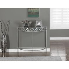 Invite a simply modern atmosphere into your home with the sleek lines and delicate design of this silver console table. The geometric detail provides a classic aspect to this unique table.