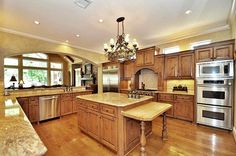 A spacious kitchen with ample sunlight and a working island with attached butcher block table. How do you like the rustic look of the cabinetry? Source: https://www.zillow.com/digs/Home-Stratosphere-boards/Luxury-Kitchens/