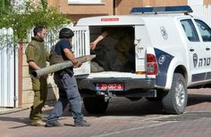 An Israeli police explosives expert carries the remains of a rocket fired from Gaza into Israel, which landed in a yard in the Southern Isr...