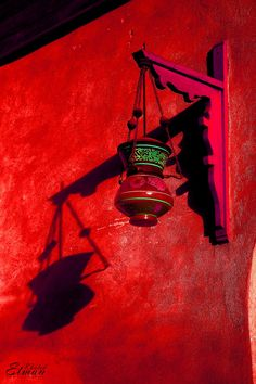 Red painted wall in Morocco and lantern