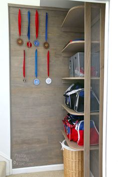 Sport Gear Storage Shelves in a Small Space | Pretty Handy Girl  One of my personal favourite DIY projects is this shelving unit for sports bag, laundry basket and hooks to hang medals on.  Brilliant use of small space.  Source for you by @DownshiftingPRO