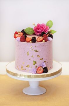 Buttercream cake with fresh berries, sugar flowers and gold leaf