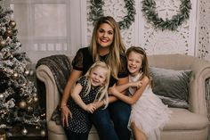 holiday mini session photo shoot christmas sisters mom family siblings neutral greenery garland tree lights screen sofa couch hugging reindeer