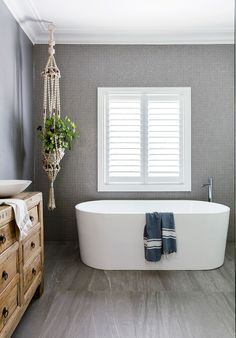 The organic appeal of macrame and turkish towels sets off contemporary bathroom fixtures.
