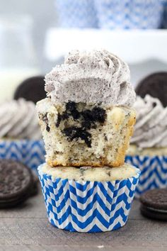 An Oreo cupcake sitting on top of another cupcake. The cupcake has a bite taken out of it, revealing the chunks of Oreo inside the vanilla cupcake. It has an Oreo buttercream