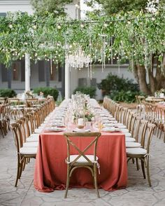 outdoor reception with banquet table under string lights and foliage. Magical!