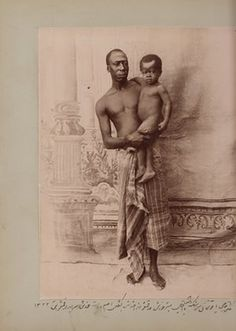 In this staged photo taken by Zell-e Soltan at his summer hunting palace near Isfahan, one of his African slaves holds his son. According to the caption, the infant (Iqbal) is the real son of the adult African slave, Haji Yaqut Khan, suggesting he wasn't a eunuch and could father his own children. The caption says that Yaqut Khan is in his ethnic clothes (languteh), which was mainly worn by Africans outside of Iran, 1904.