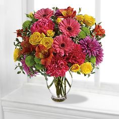 This is a Floral bouquet/arrangement with yellow #roses, pink #gerberas, orange #alstroemeria, hot pink #carnations, green button #chrysanthemums and purple cushion spray chrysanthemums are accented with oregonia in a glass vase.