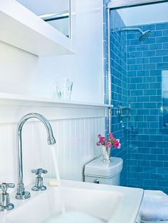 Ocean blue subway tiles line the shower and give this streamlined bathroom a splash of color. White wainscoting and simple fixtures give it casual, cottage style. (Photo: Thomas J. Story)