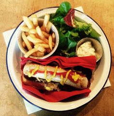 Bratwurst in a toasted brioche roll, with fried onion, mustard and ketchup. Salad, Mayo, fries on the side.