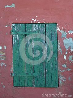 A green window on a grunge pink-red wall texture, traditional image of the buildings in reconstruction.