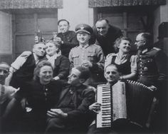 Group portrait of T-4 Euthanasia program personnel at a social gathering.  One of them plays the accordian.