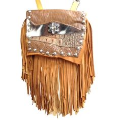 "GOLDEN DAISY MARTY - silky soft, made of gold deerskin with a 7"" gold and tobacco deerskin fringe. The centerpiece is a silver flower with a golden jewel. It's surrounded by brown and white hair-on-hide cow, genuine ostrich and printed leather. Etched silver metal studs adorn the flap. Wear bag clipped to belt loops for hands-free carrying of your essentials. Interior includes a leather strap. Add the strap when you want a completely different look."