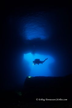 Silouette diver inside cathedral cave.