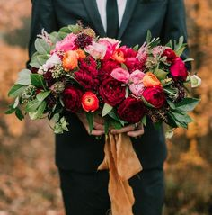 A loose asymmetrical bouquet of Darcey garden roses, Juliet garden roses, Romantic Antique garden roses, burgundy scabiosa, light pink astilbe, peach ranunculus, pink pepper berry, jasmine vine, bay laurel, and seeded eucalyptus wrapped in gold glitter ribbon tied in a bow.