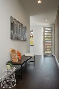Glass striped front door, dark wood floors, wood bench, abstract art, wire side table | Noble Ridge Construction, Inc.