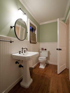 Wainscoting/paneling, pedestal sink, round mirror