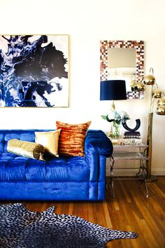 Blue velvet sofa with graphic art and colorful mirror
