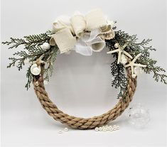 """Beach Christmas decor rope wreath, tons of beachy charm for Christmas and for year-round! This sweet little rope wreath form has a metal core for strength covered in real rustic jute roping.  PVC cypress greens and an organza and linen bow, then added little white finger starfish, pearly turban shells, and a sprinkling of the teeny tiny natural umbonium seashells.   DON'T put it away after Christmas!  Built on an 11"""" wreath form, with the spread of the greenery around 13"""" total diameter."""