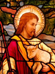 Stained glass painting of Jesus holding a lamb