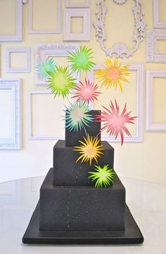 Black wedding cake with fireworks!  Love the idea of a black wedding cake and fireworks.  Maybe a punch of green and silver bands at the bottom of the layers.  I also like the topsy turvy cakes as apposed to the traditional absolutely perfectly aligned cakes.