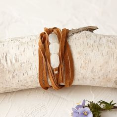 """Shimmering moonstones center this supple, natural leather wrap bracelet, each one hand-crafted by Ria B.- Natural suede, moonstone- Rivets contain nickel- Stones 2"""" total width- Double knot for best hold during use- Handmade in the USA44""""L"""