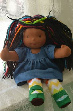 This is Paris, a Bamboletta Sitting Friend.  She has dark skin, long hair made with mohair and wool yarns in a black color with black and rainbow dreadlocks and brown eyes.  She is wearing the pictured outfit, underpants and wool felt shoes.