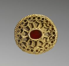4th-5th century (Early Medieval). This is an oval openwork fibula set with a carnelian and decorated with a geometric pattern of gold wire. The openwork cells were likely filled with stone insets originally. The gold beading along the edge is characteristic of Hunnish craftsmanship.