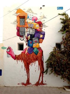 "by Brusk (partialy ~ by eL Seed) ""Camelhood"" in in the village of Erriadh, on the Tunisian island of Djerba, on August 8, 2014, as part of the artistic project Djerbahood. *eL Seed (born 1981) is a French-Tunisian street artist whose works incorporate traditional Arabic calligraphy, a style he calls 'calligraffiti.'"