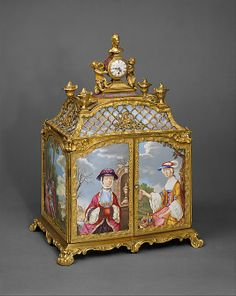 Jewel cabinet with watch, 1765, England. Purveyor: James Cox  (ca. 1723–1800). The enamels on the side of the cabinet were adapted from prints of paintings by Antoine Watteau (1684–1721) and François Boucher (1703–1770). With characteristic inventiveness, Cox included a secret drawer above the more obvious drawers that is released by means of a jeweled button on the back of the cabinet. The watch is supported by two playful cherubs of cast and painted brass and surmounted by a bust of a…