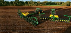 Tractors and planters parked in a field.These are the new John Deere ExactEmerge & MaxEmerge 5 corn planters as pictured in the EE & ME 5 brochure