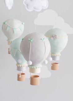 Género neutro bebé móvil, globos en menta y gris con Marfil para la decoración de su dormitorio. Ideal para un viaje de niños del tema. Pequeños globos de aire caliente flotando bajo dos nubes pequeñas. Cuelgan de una tapa móvil de madera. Cada globo tiene diversos adornos de arcos