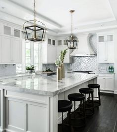 White Kitchen. White kitchen cabinet. White kitchen with stacked wall cabinets, custom range hood, and large island with plenty of seating. White Cabinets: The whites were matched. The color was a standard option with Wood-mode cabinetry called Nordic White. It's a soft white, not too bright. Signature Interior Designs