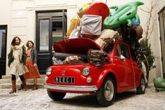 Shoppers walk near a vintage Fiat 500 car in the courtyard of Paris's newest concept store, `Merci` or `Thank You`, located on three floors of a 1920's industrial building on March 16, 2009.