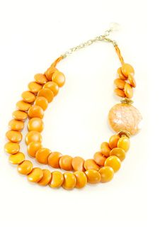 "A pop of color sure looks nice with a funky-printed blouse or a simple white tank. This Orange Beaded Necklace is a perfect ""pop"" for that purpose."