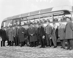 New England manager Alf Ramsey stands in front of the team bus with his squad of players as they arrive at the RAF Arena in Stanmore Park, for a training session in preparation for the friendly international match against France at Wembley Stadium. 13th February 1963.