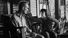 Robert Duvall as Boo Radley on the porch swing with Scout.-- with Mary Badham as Scout, from 'To Kill a Mockingbird', 1962