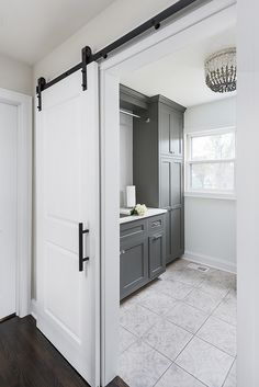 Home Renovation Design Grey laundry room Renovated Laundry room Upstairs you will find a newly-renovated laundry room with sliding barn door and dark grey cabinets. Trim, walls and barn door are painted in Benjamin Moore Super White Grey Laundry Rooms, Laundry Room Doors, Interior Barn Doors, Home Interior, Home Renovation, Home Remodeling, Bathroom Renovations, Basement Renovations, Small Bathroom