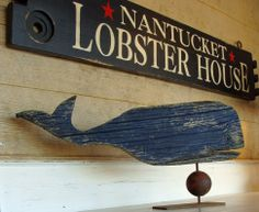 """A weathered folk art blue whale on stand is displayed on a painted sideboard with a custom made """"NANTUCKET LOBSTER HOUSE"""" sign above."""