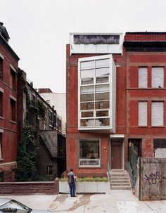 """Yvette Leeper-Bueno and Adrian Bueno's home, on West 112th Street in New York City, is recognizable by its two-story bay window angled to bring light and views into the dark, narrow structure. """"There's a threshold of planting between the outside and inside,"""" says architect Laura Briggs, citing the blooming boxes on the sidewalk, the rear deck, and the master-suite terrace (above the bay window). Photo by Adam Friedberg. See how the rooms stack up inside the narrow shell."""