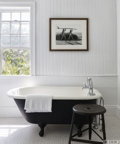 A chic black and white tub with Waterworks fittings sits in an all white bathroom inside of a Hamptons summer house.
