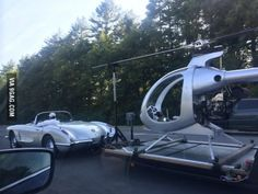 50's corvette towing a helicopter.