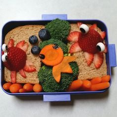 Under the sea bento: carrot fish blowing blueberry bubbles in the middle. A strawberry crab on the left, and a strawberry squid on the right. All on top of an egg salad sandwich.  #bento